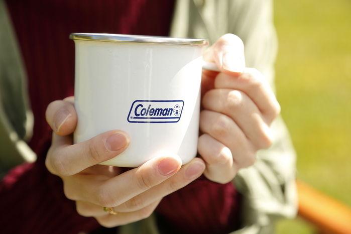 コールマンのマグカップを持っている手元