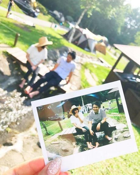カップルが楽しそうに話す様子を収めた写真を手にもち撮った写真