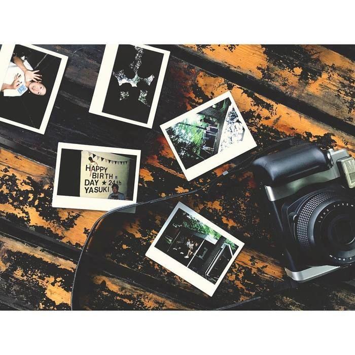 テーブルの上に置かれたキャンプの思い出の写真とカメラ