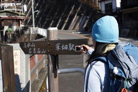 高水山岩葺石山と軍畑駅方面に分かれる案内表の写真を撮る女性