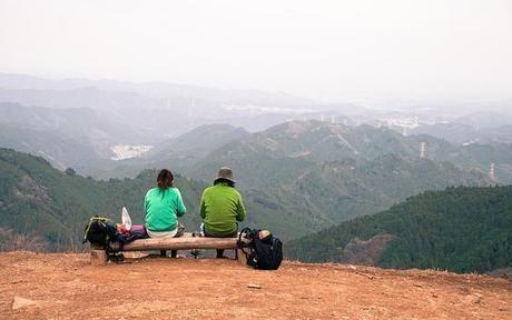 山頂でベンチに座り食事をする2人組