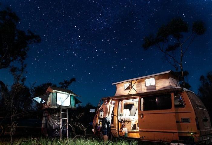 夜の九十九里オートキャンプ場でトレーラーハウスを使いキャンプをしている人