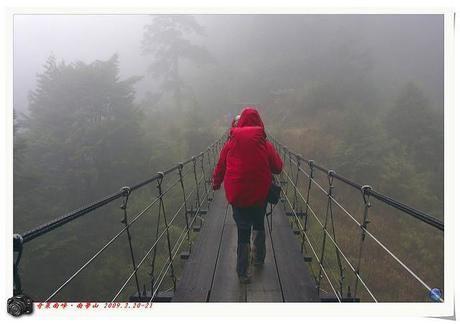 悪天候の中レインウェアを着て橋を渡る人