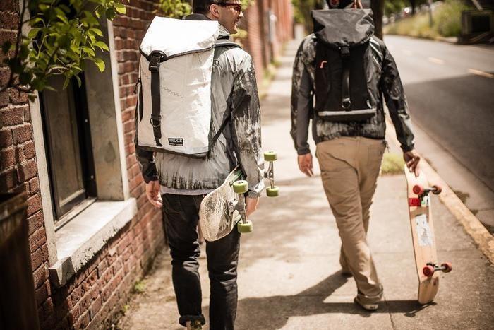 スケボーを持ちリュックを背負っている2人の男性