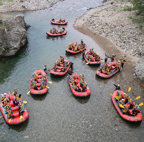 たくさんのボートで人々がラフティングを楽しんでいる様子