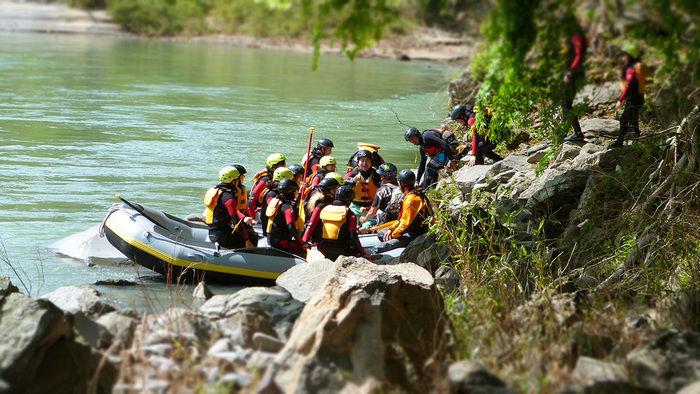 ラフティングでボートから岸に降りようとしている人々