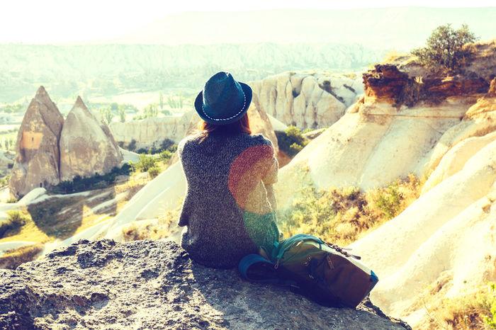 太陽に照らされながら山を見ている帽子をかぶった女性