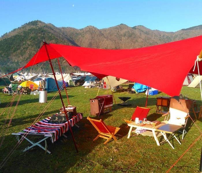 赤いタープに合わせて作られた赤いローチェアを使いキャンプをしている様子