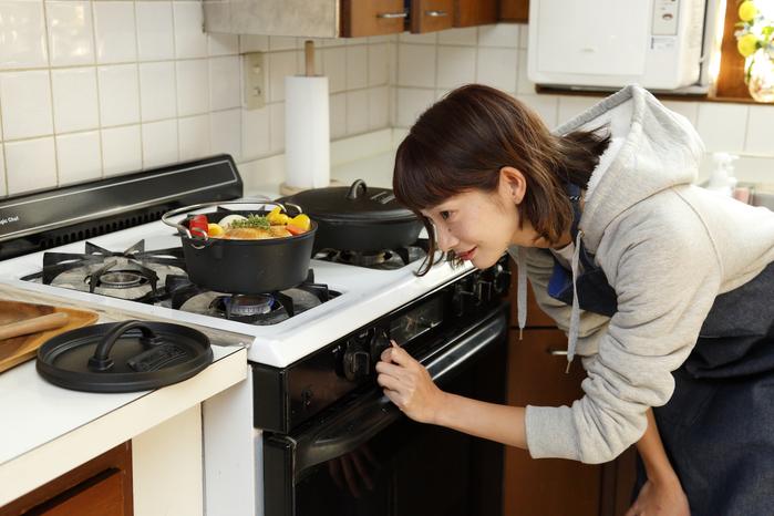 料理の火加減を見る女性