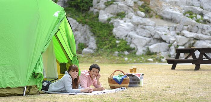 白崎海洋公園にテントを張り男女が寝転がって入り口から顔を出している様子