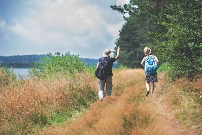 山を散策するスカートを穿いた女性と男性