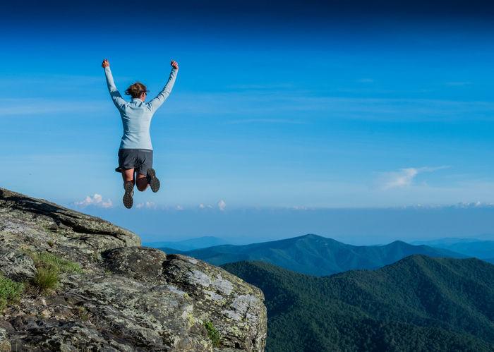 山の山頂でジャンプをする女性