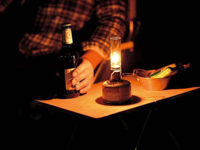 夜にガスランタンで明かりを灯し酒を楽しんでいる様子