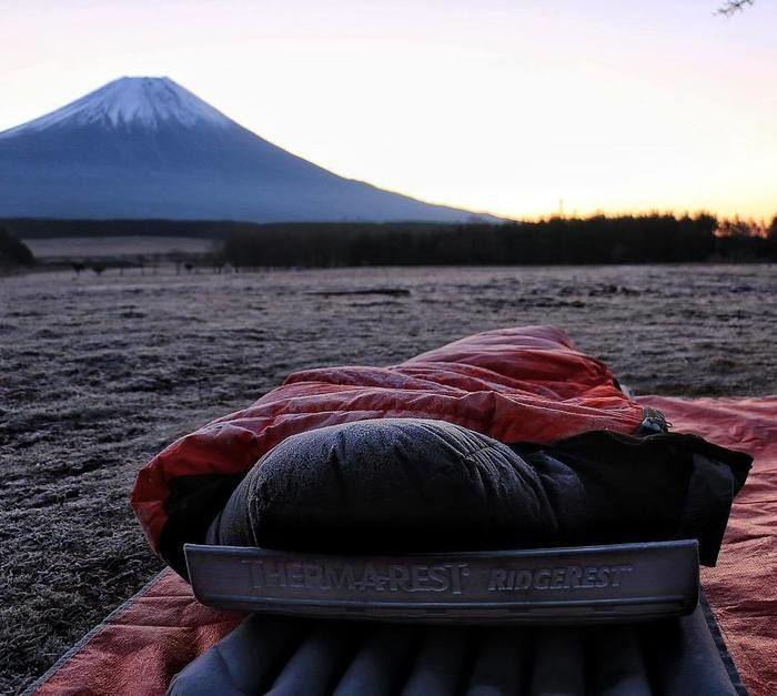富士山を背景に地面に設置された寝袋