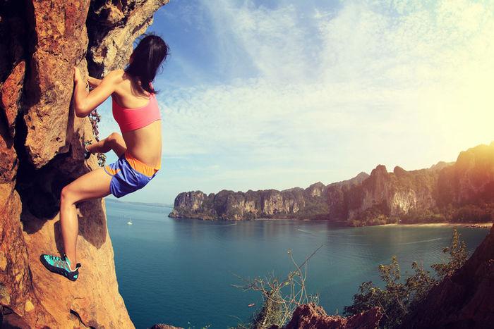 海を背に岩を登る女性