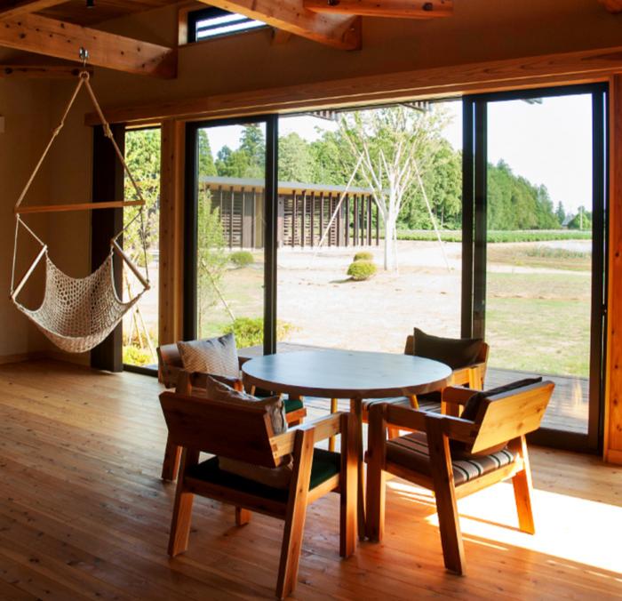 ハンモックや木の椅子やテーブルがあるTHE FARMのコテージ内の様子