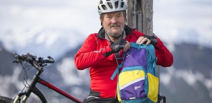 ドイターのリュックを持って座るサイクリストの男性