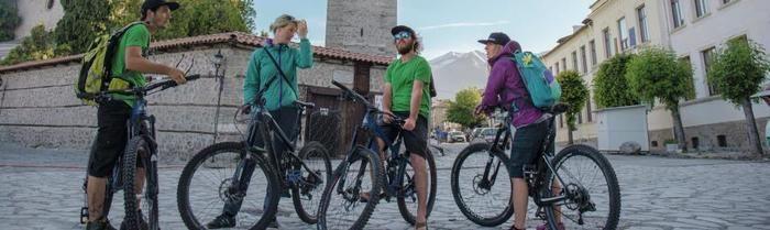 ドイターのリュックを背負って自転車に跨り、話をする人々