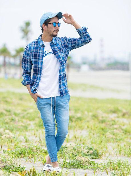 白Tに青チェックシャツを羽織るクールなコーディネートの男性