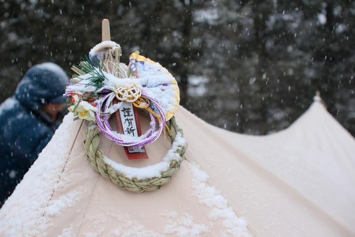 テントの正月飾りに降る雪