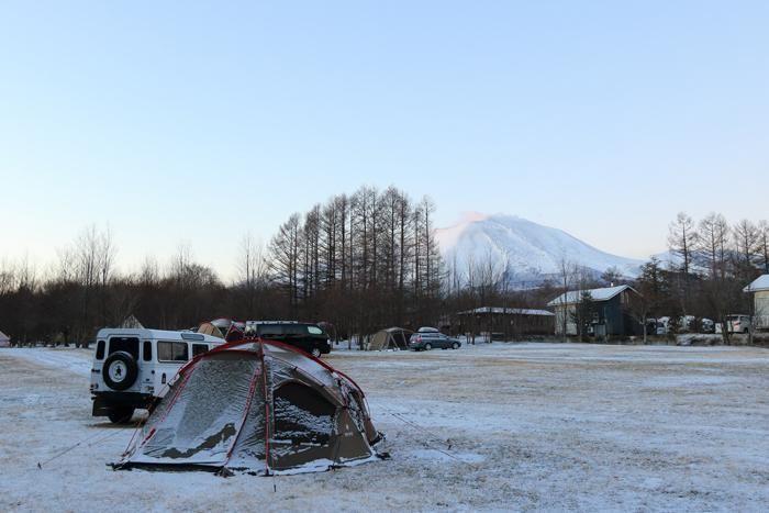 雪の残るキャンプ場とテント