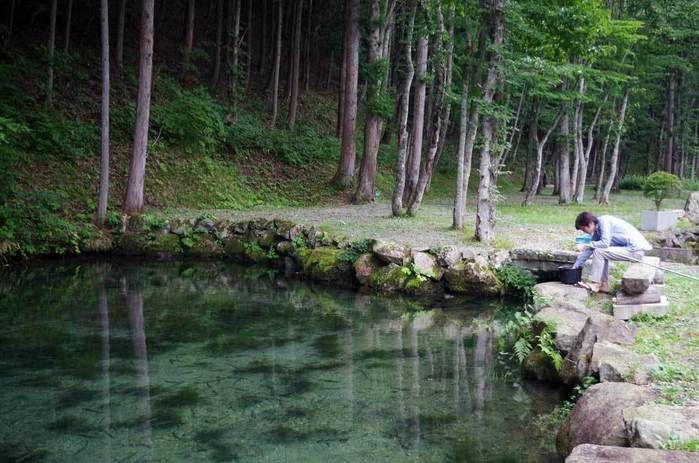 ナラ入沢渓流釣りキャンプ場の清流で釣りを楽しむ人
