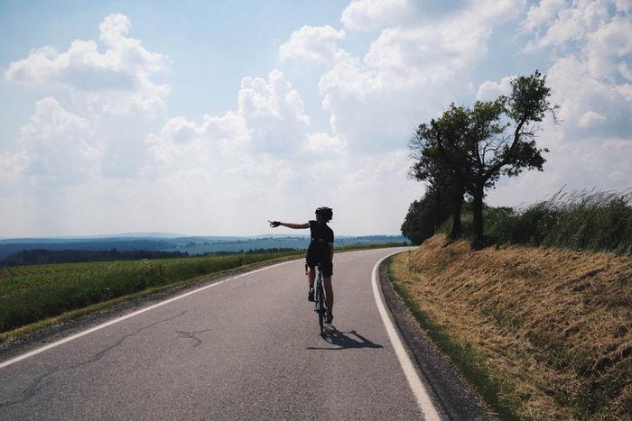 自転車に乗り指を指している人