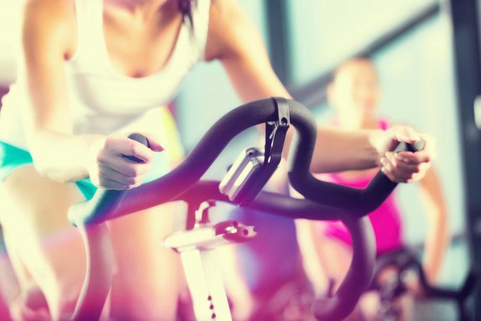 フィットネスジムでバイクを漕いでいる女性