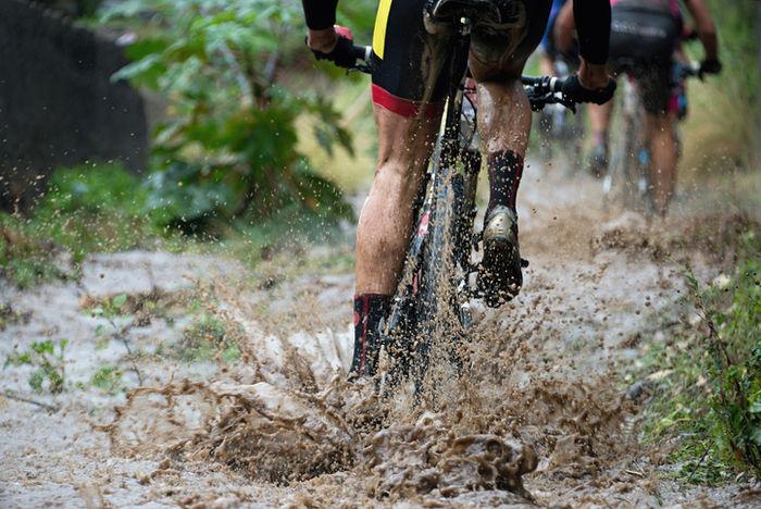 泥道を自転車で走っている人