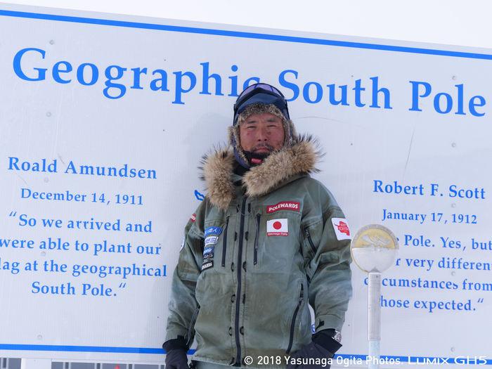 南極地点の看板を背景に記念撮影する荻田泰永さん