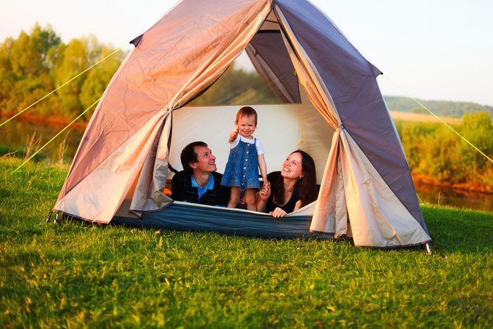 小さい女の子と両親がテントの中にいる