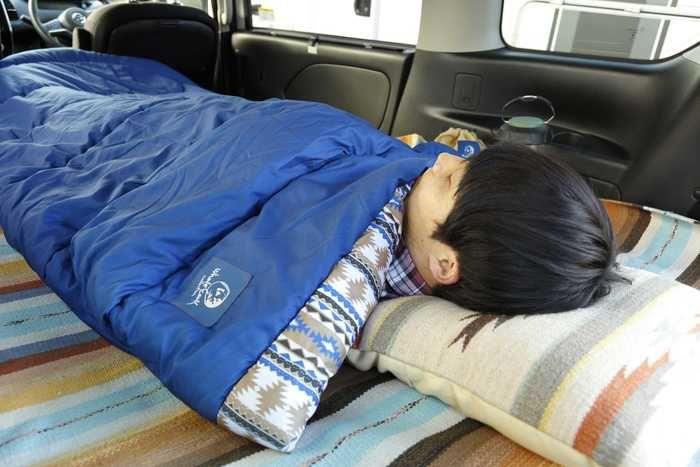 封筒型シュラフを使って眠る男性