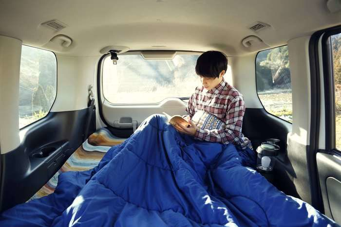 封筒型シュラフを膝にかけて車内でくつろぐ人