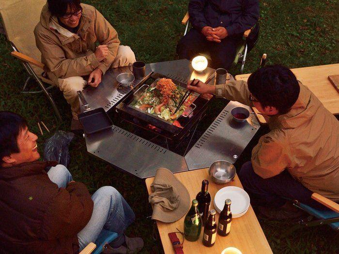 ジカロテーブルを囲みキャンプをしている人たち