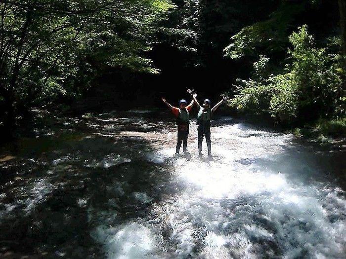 桐の木平キャンプ場の川で手をあげている2人