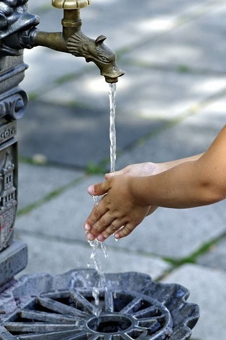 水道で手を洗っている人