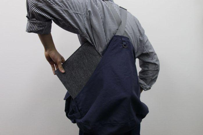 タキビベストの背面ポケットにノートパソコンを入れてる様子