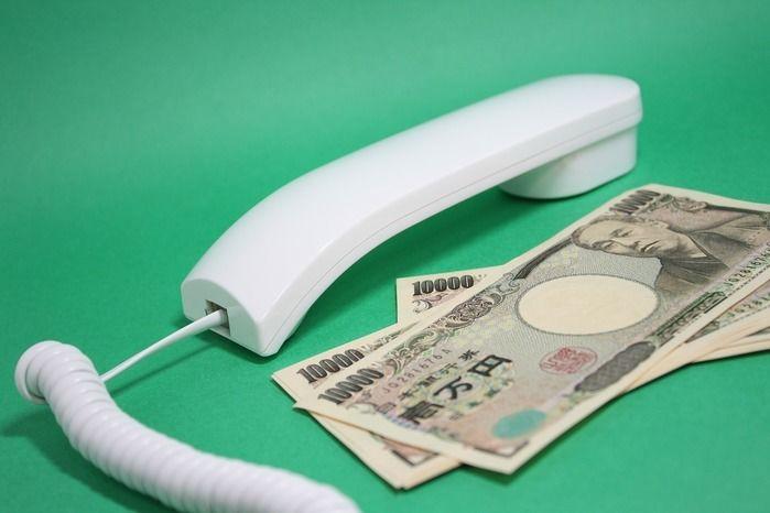 電話の受話器と横に置かれた一万円札