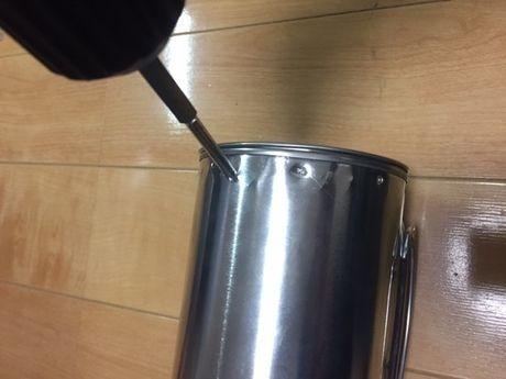 缶の側面に空気穴を開けている様子