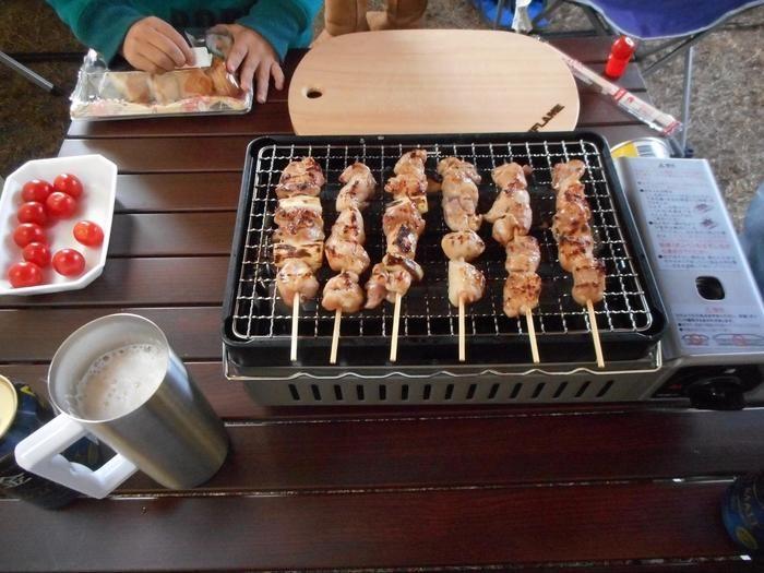 網に串刺しにした鶏肉を置いて焼き鳥を作っている様子