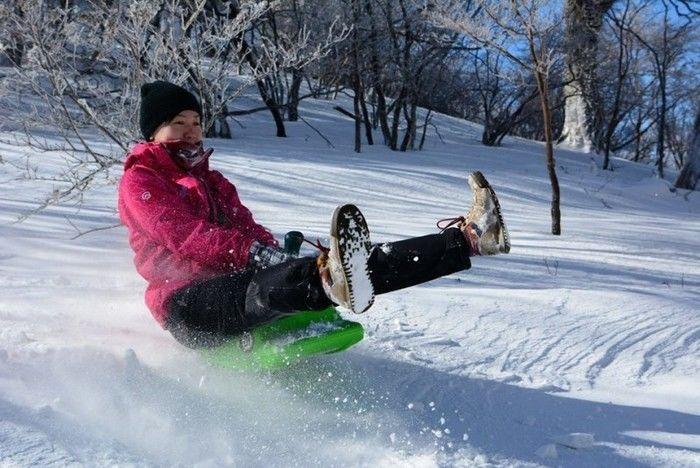 服掛松キャンプ場で雪遊びをする人
