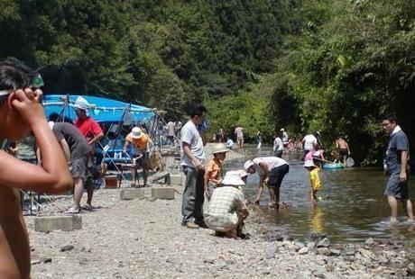 八曽モミの木キャンプ場で川遊びとバーベキューをする人々