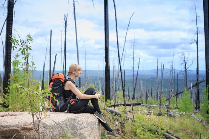岩の上に腰掛け、片足を抱える女性