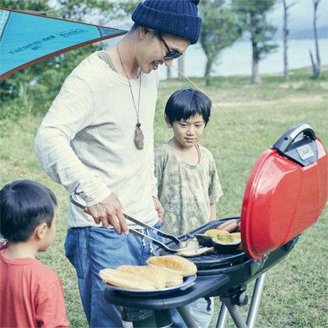 父親と子供がグリルでバーベキューをしている