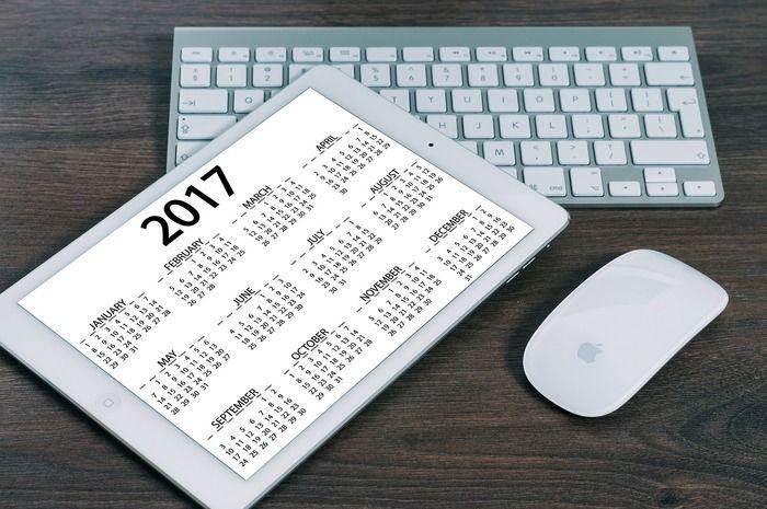 キーボードの上に置かれたカレンダーとマウス