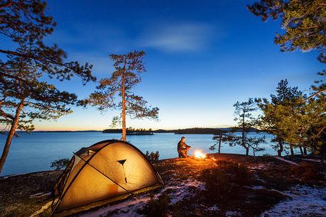 湖畔のテントサイトで夕暮れに火をおこす男性