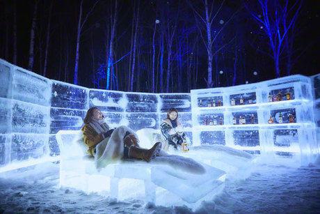 アイスヴィレッジの氷のベッドでくつろぐ女性