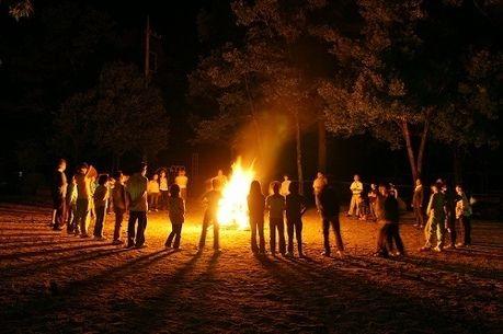 キャンプファイヤーで火を囲み立っている人々
