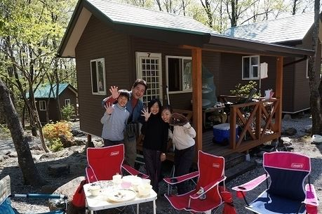 バンガローの前でキャンプを楽しむ家族