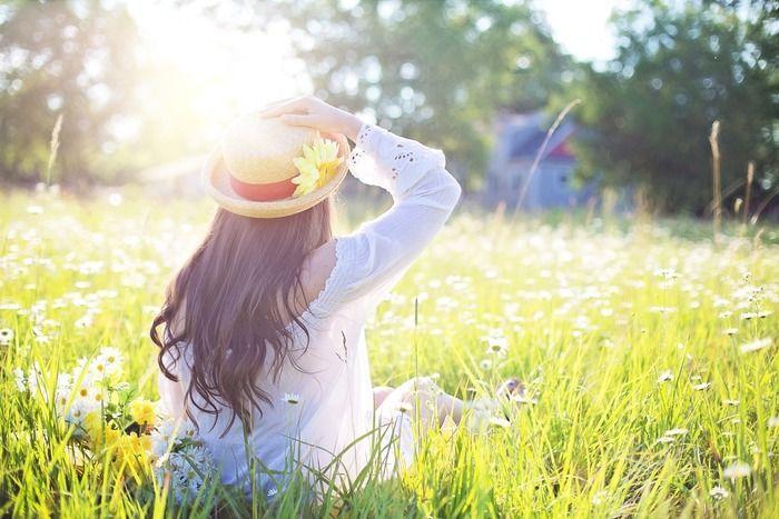 草原に座り帽子を抑えている女性